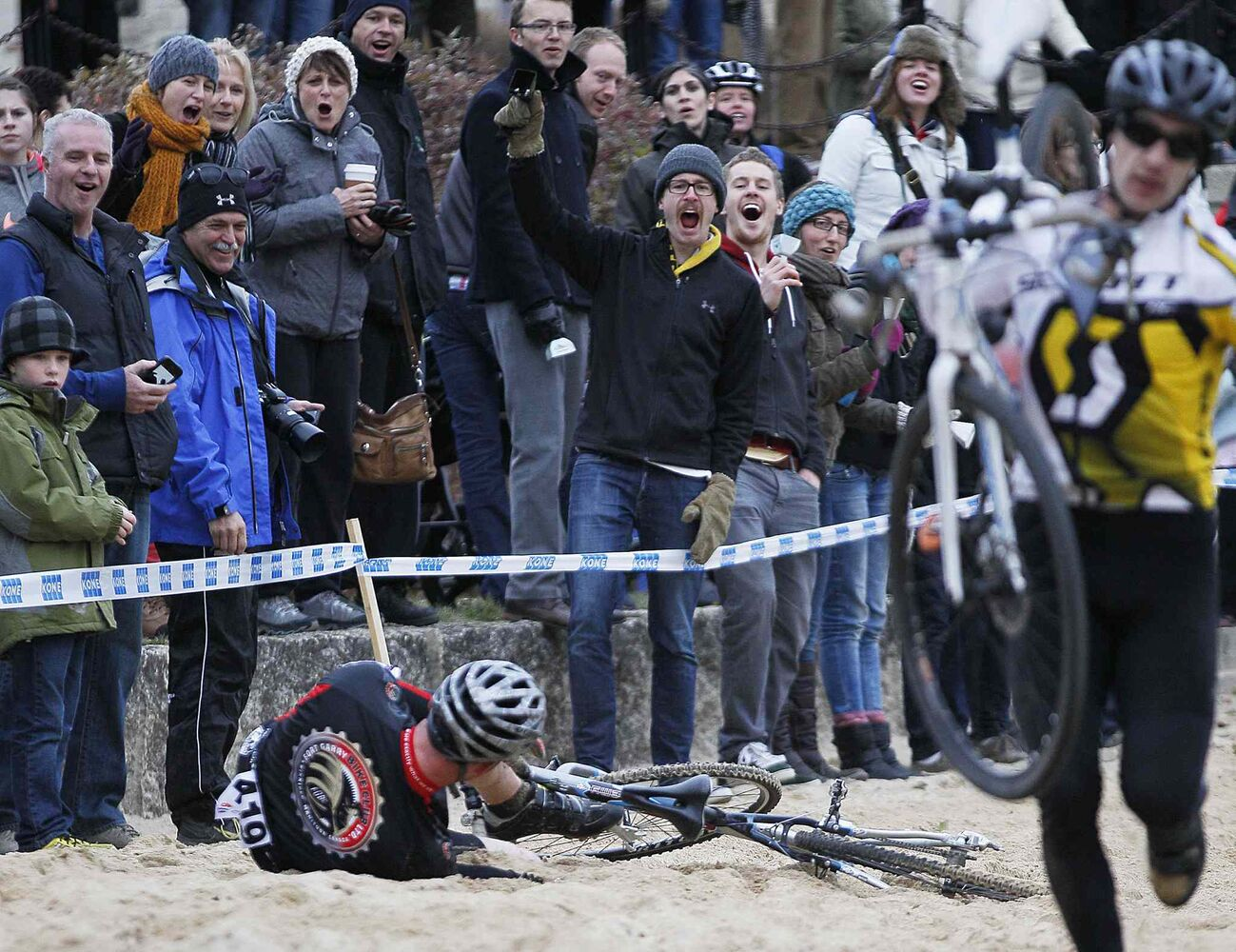 Fans react as Luke Enns (419) takes a spill in the sandpit. (John Woods / Winnipeg Free Press)