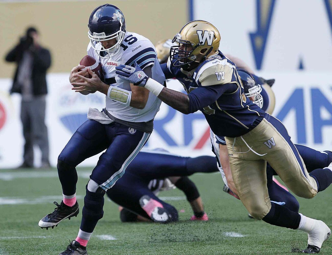 Toronto Argonauts' quarterback Ricky Ray (15) gets sacked by Winnipeg Blue Bombers' Michael McAdoo (98) during the first half.