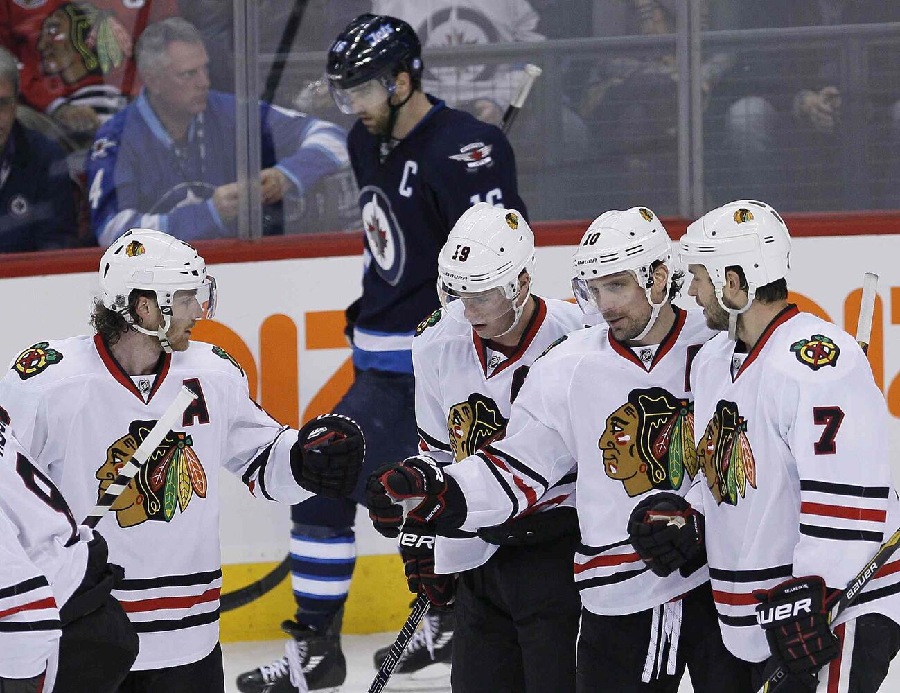 Chicago Blackhawks (from left) Duncan Keith, Jonathan Toews, Patrick Sharp and Brent Seabrook celebrate Sharp's empty-net goal against the Winnipeg Jets during the third period as Jets captain Andrew Ladd skates by.