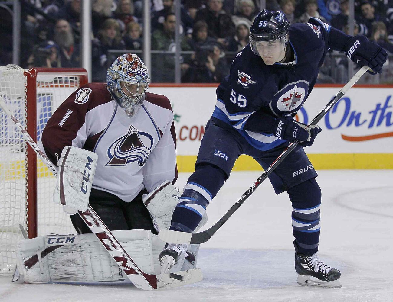 Winnipeg Jets forward Mark Scheifele (right) attempts to deflect the shot past Colorado Avalanche goaltender Semyon Varlamov during the second period.