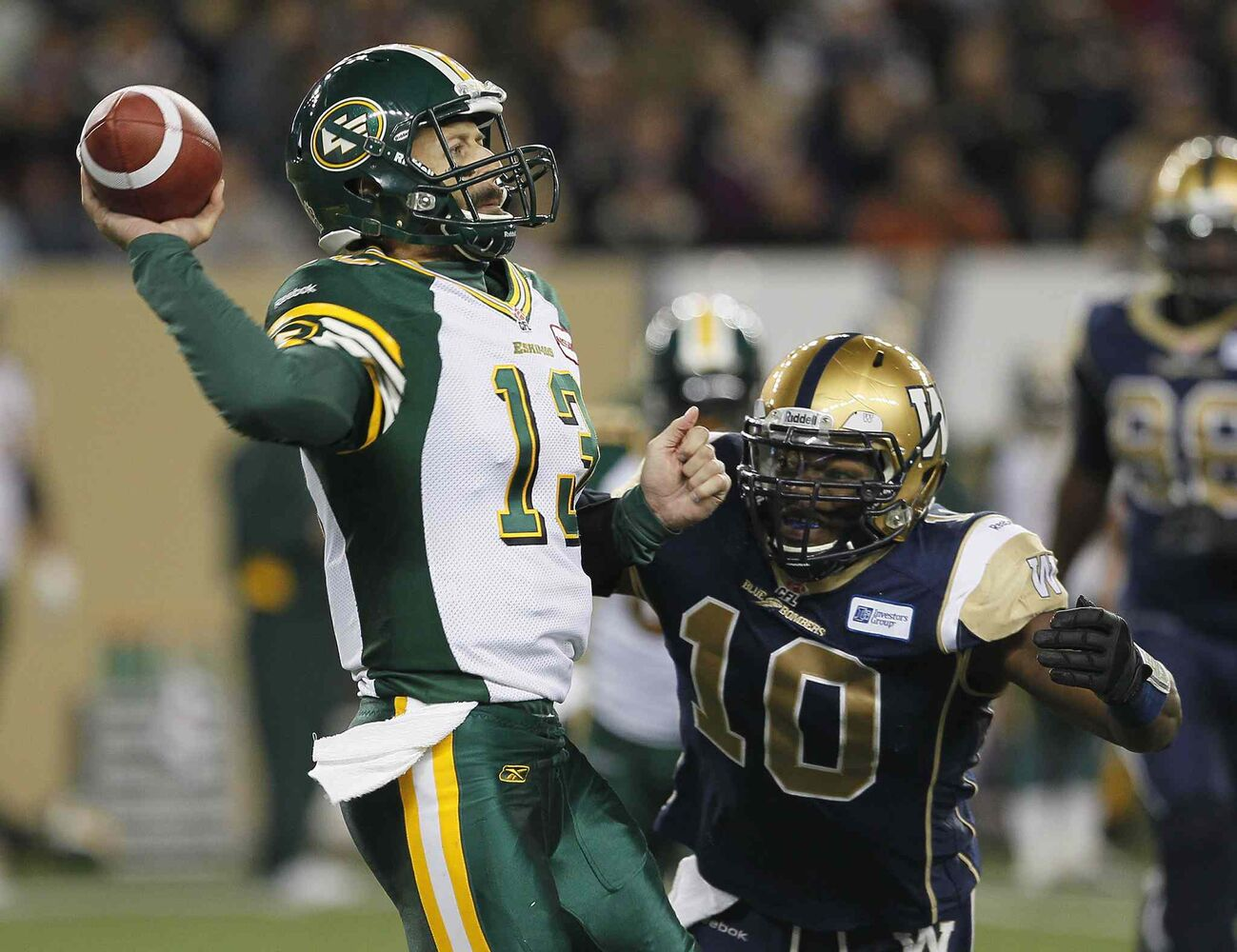 Edmonton Eskimos' quarterback Mike Reilly (left) gets a pass away under pressure from Winnipeg Blue Bombers' Henoc Muamba. (John Woods / The Canadian Press)