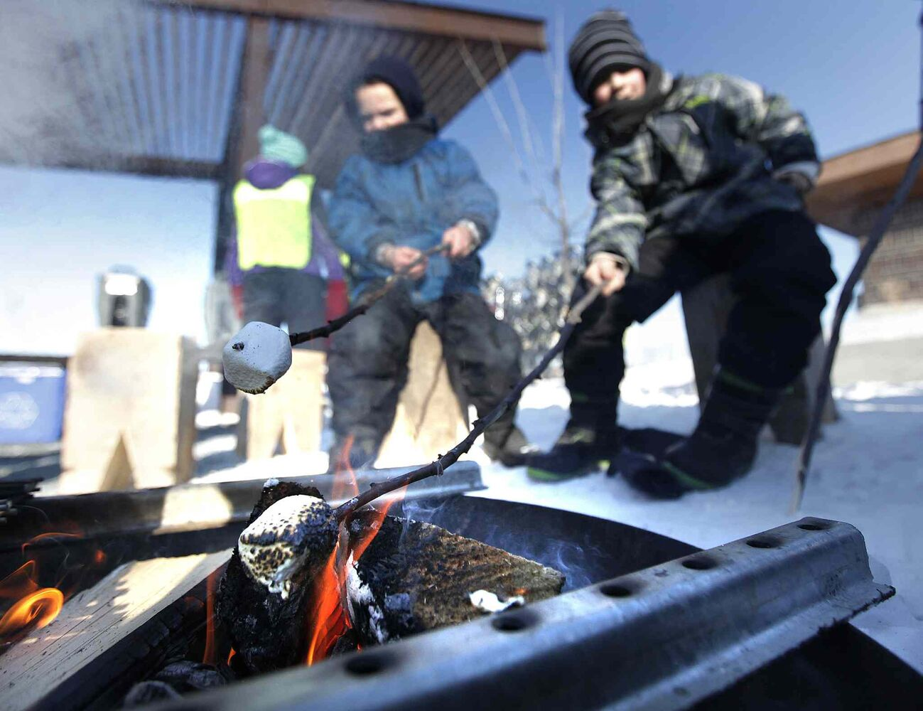 Colby (left) and Jesse Squires roast marshmallows at Snow Trek.