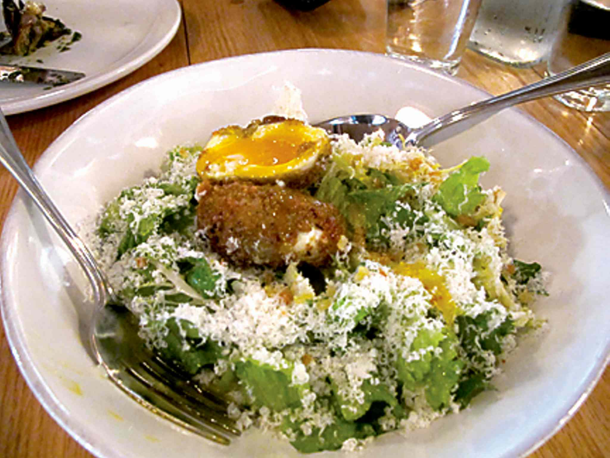 Caesar salad with deep-fried egg from Mani Osteria & Bar.