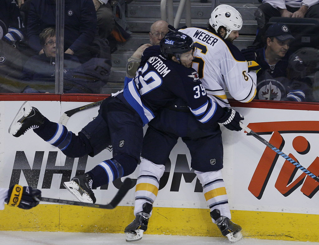 Winnipeg Jets' Tobias Enstrom (#39) and Buffalo Sabres' Mike Weber (#6) crash into each other during third period NHL action in Winnipeg Tuesday.