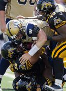 Winnipeg Blue Bombers quarterback Justin Goltz (third from bottom) is sacked by Hamilton Tiger-Cats' Torrey Davis (bottom), Hasan Hazime (second from bottom), and Eric Norwood (top) during the fourth quarter of Saturday's game in Guelph.