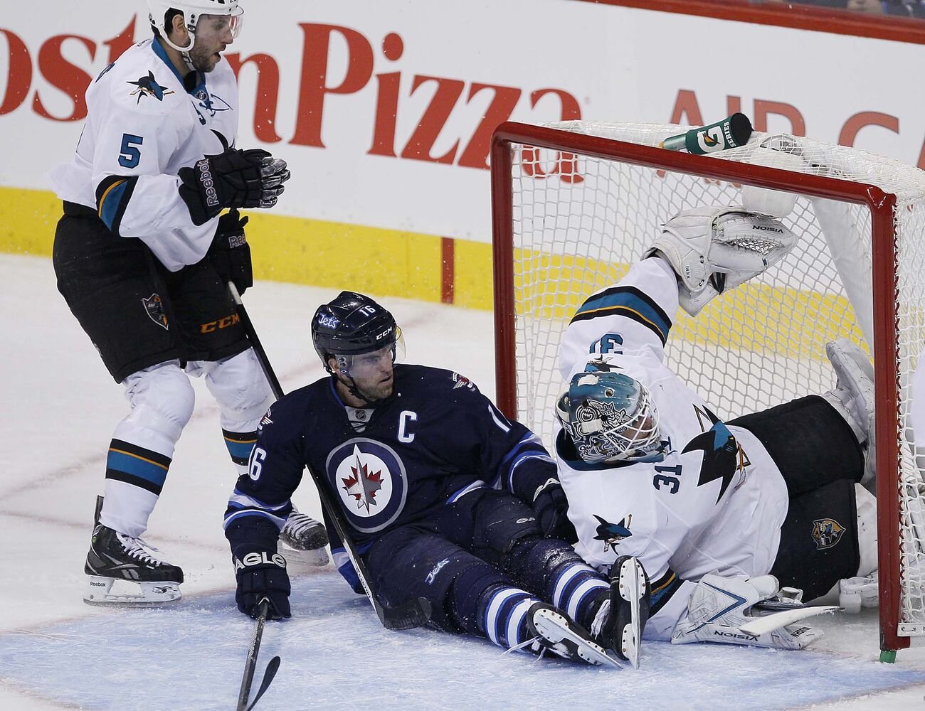 Winnipeg Jets' Andrew Ladd (16)¤ crashes into San Jose Sharks' goaltender Antti Niemi (31) after being hooked by Sharks' Jason Demers (5) in third period action.