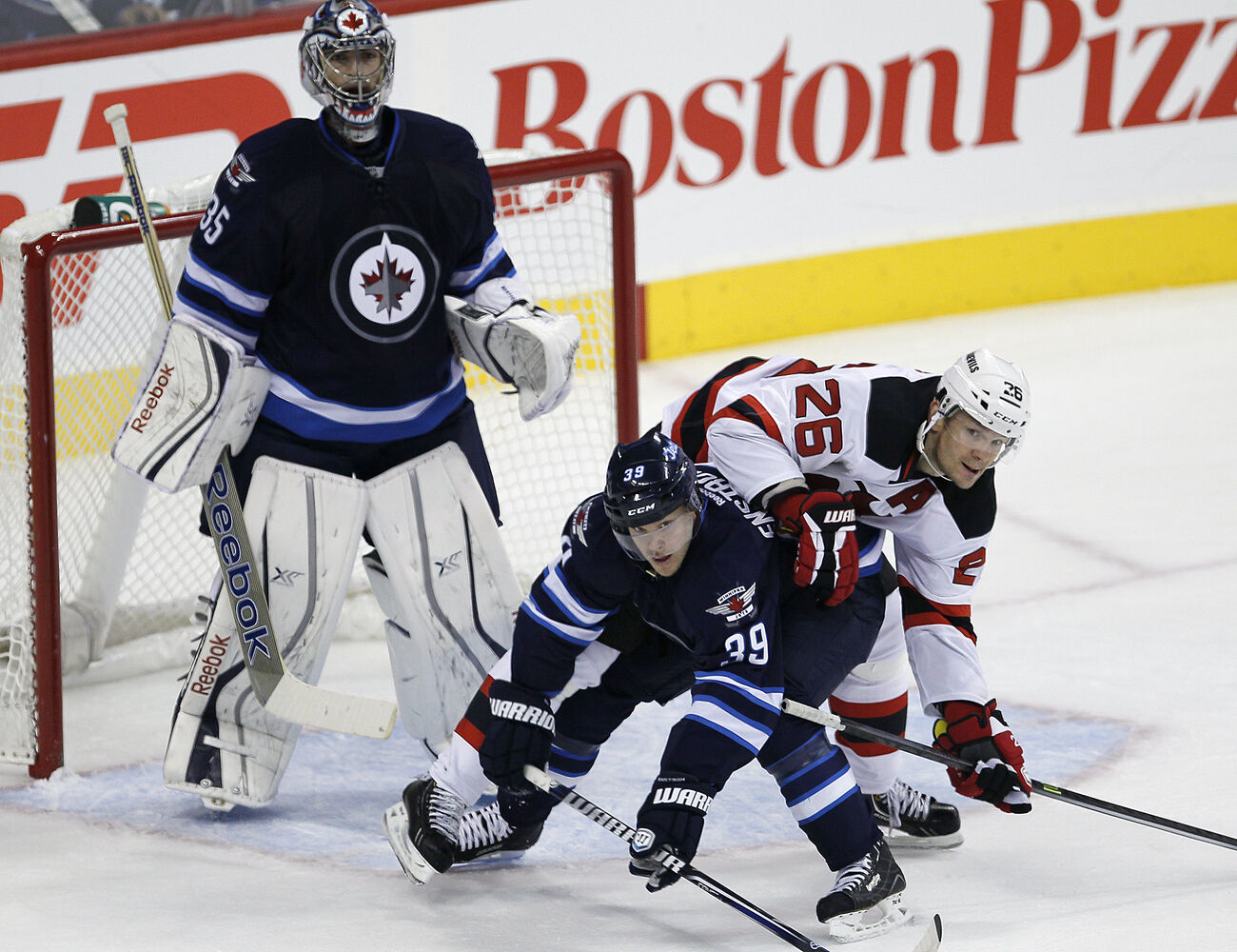 Patrik Elias goes over the top of Toby Enstrom as goaltender Al Montoya stands by during the first period.
