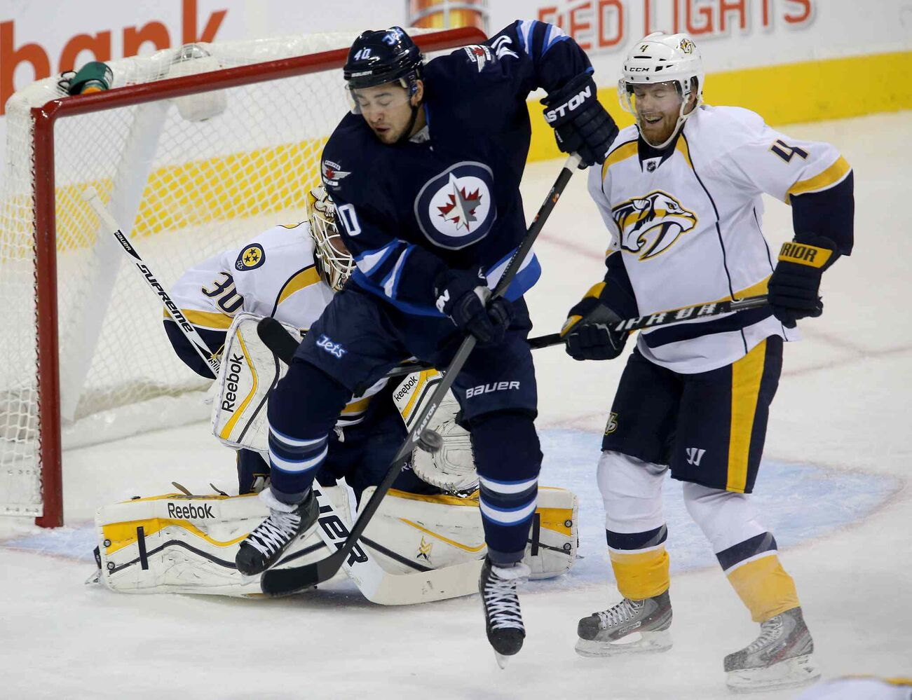 Winnipeg Jets' Devin Setoguchi screens a shot through his legs in front of Nashville Predators' goaltender Carter Hutton (30) and Ryan Ellis (4) during the first period.