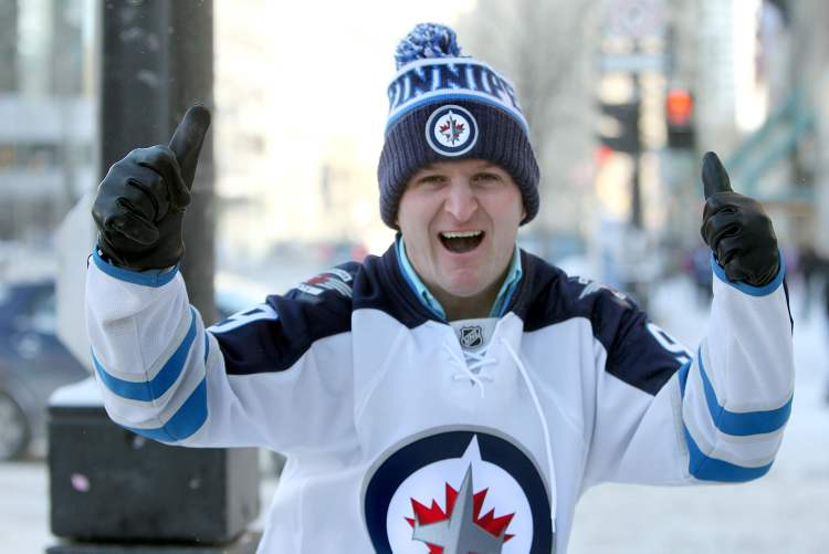 Winnipeg Jets fan Luke Wiebe cheers on his team and gives the two-thumbs-up as he rushes across Portage Avenue at Donald Street heading to the Jets game at the MTS Centre with his brother Nathan.  This is the first NHL Jets game of the season after a long lockout. (RUTH BONNEVILLE / WINNIPEG FREE PRESS)
