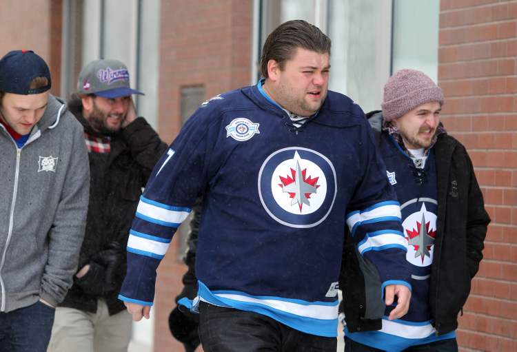 Winnipeg Jets fans brave the weather on one of Winnipeg's coldest days wearing their Jets jerseys as they make their way down Donald Street Saturday to the first Winnipeg Jets, NHL game of the season.  (RUTH BONNEVILLE / WINNIPEG FREE PRESS)