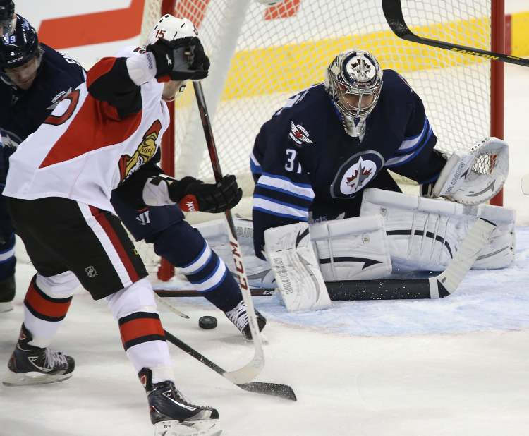 Winnipeg Jets' goaltender Ondrej Pavelec (31) stops Ottawa Senators' Zach Smith (15) during the first period.