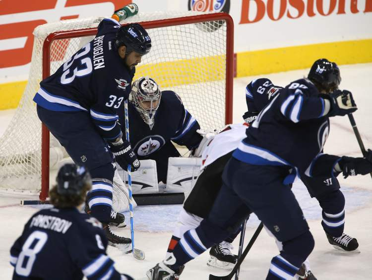 Winnipeg Jets' goaltender Ondrej Pavelec (31) peaks through the crowd as the team hosts the Ottawa Senators' in the first game of the season at MTS Centre, Saturday.