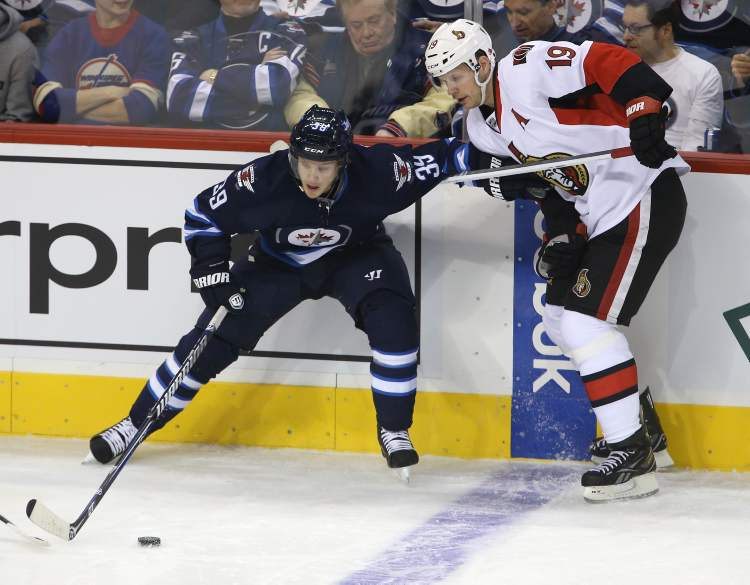 Winnipeg Jets' Tobias Enstrom (39) battles with Ottawa Senators' Jason Spezza (19) during the first period in the first game of the season.