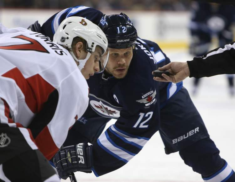 Winnipeg Jets' Olli Jokinen eyes the puck prior to a face-off against Ottawa Senators' Kyle Turris during the second period of play at MTS Centre Saturday.
