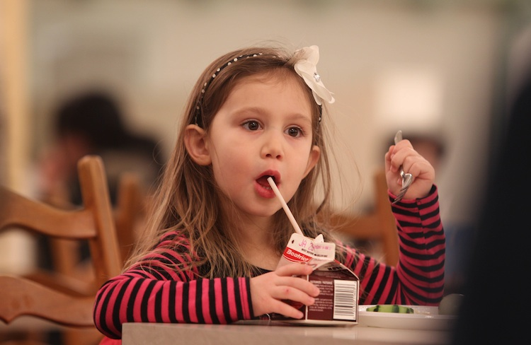 Four-year-old Mia Reynolds sips on her chocolate milk while having lunch with her mom Wednesday.