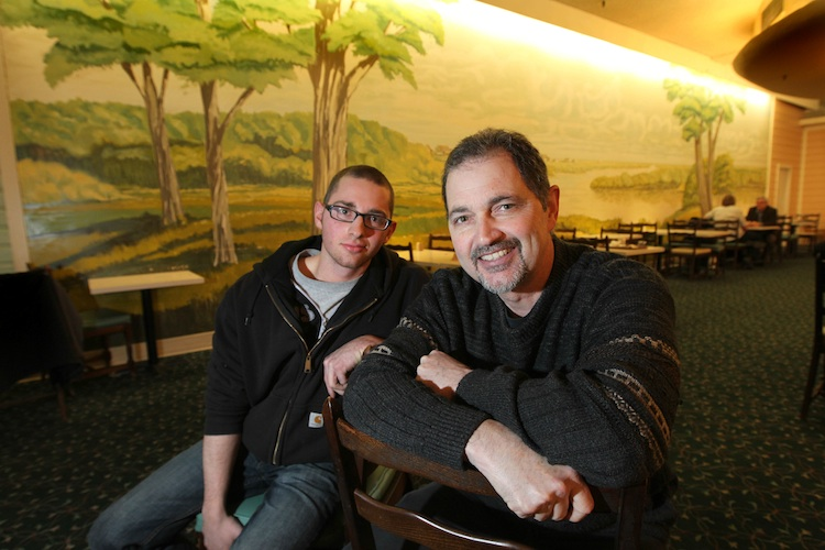 John Waagenaar and his son Wess sit next to the mural his dad painted in the early 1970s. (Ruth Bonneville / Winnipeg Free Press)