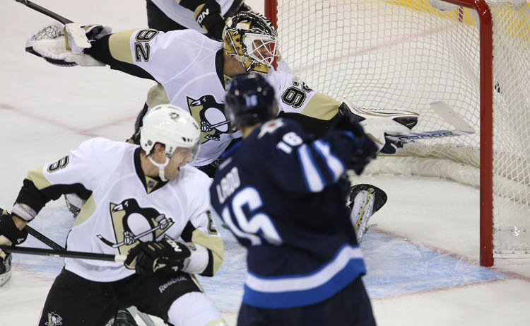 Winnipeg Jets' Andrew Ladd (16) puts the puck past an outstretched Pittsburgh Penguins' goaltender Tomas Vokoun during the second period of play.