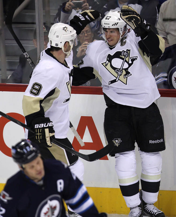 Penguins captain Sidney Crosby celebrates scoring his second of two goals with teammate Pascal Dupuis during the first period against the Jets Friday in Winnipeg.