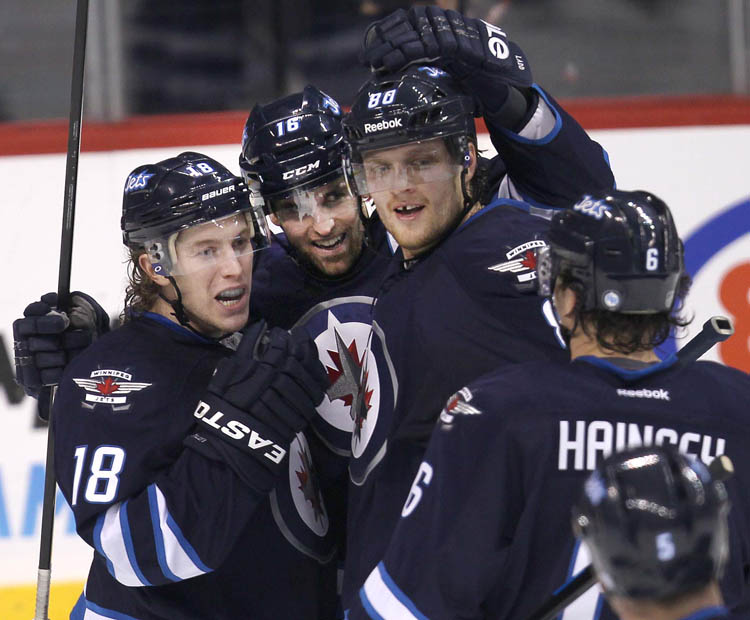 Winnipeg Jets Bryan Little, Andrew Ladd, and Nik Andtropov wait for teammate Ron Hainsey to join their celebration after the Jets took a 3-2 lead with a goal from Ladd.