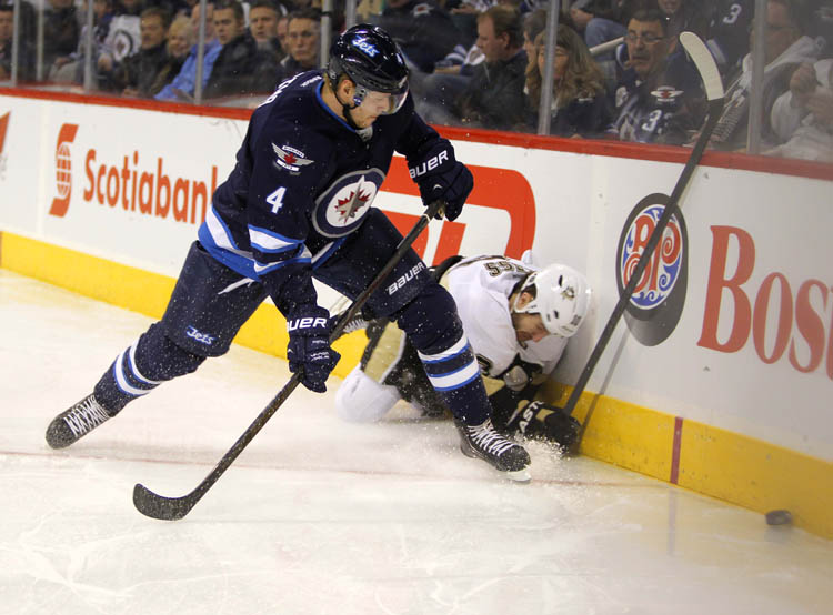 Jets' Paul Postma goes for the puck after Pittsburgh Penguins Tanner Glass crashed to the ice. (Boris Minkevich / Winnipeg Free Press)