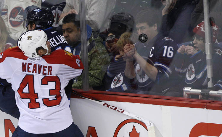 Fans react to the puck hitting the glass as Winnipeg Jets Kyle Wellwood and Florida Panthers Mike Weaver crash into the boards during overtime at MTS Centre in Winnipeg Tuesday night.