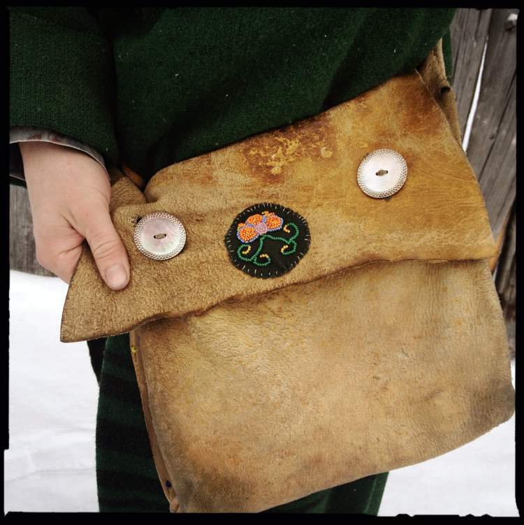 The leather handbag is essentially a 19th-Century European version of a man-purse. This one's made of cow leather, but in 1815 it would have been moose, deer or elk. The abalone buttons would have been traded up from the Gulf of Mexico.