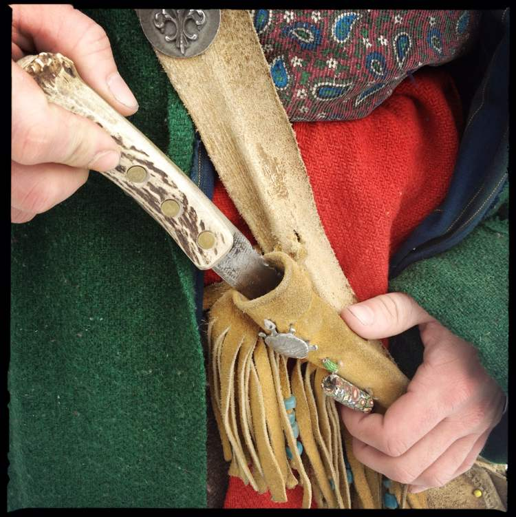The dagger in the sheath has an antler handle and a metal blade fashioned from an old or worn-out file. It was more of a utility knife than a weapon. The fringes on the leather sheath are adorned with beads known as blue padres. The hands that grasped the tool would have been clad in leather gauntlets.
