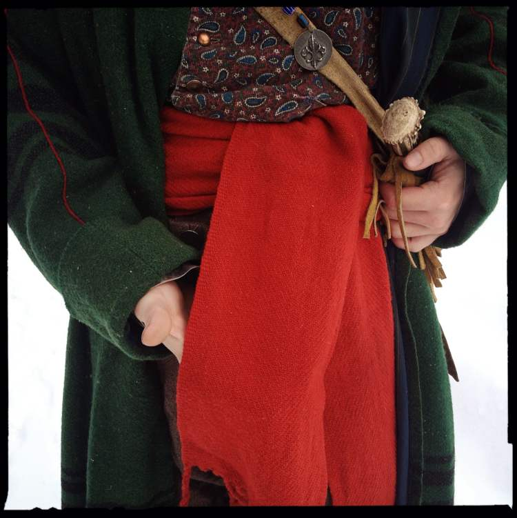 Contrary to popular belief, the red wool sash is not ornamental. It was wrapped tightly around a voyageur's waist to prevent hernias while carrying heavy loads, functioning much like a modern weightlifter's belt. The end of the sash, however, would have been tucked in. Otherwise, it would have gotten caught on a branch at the first portage.