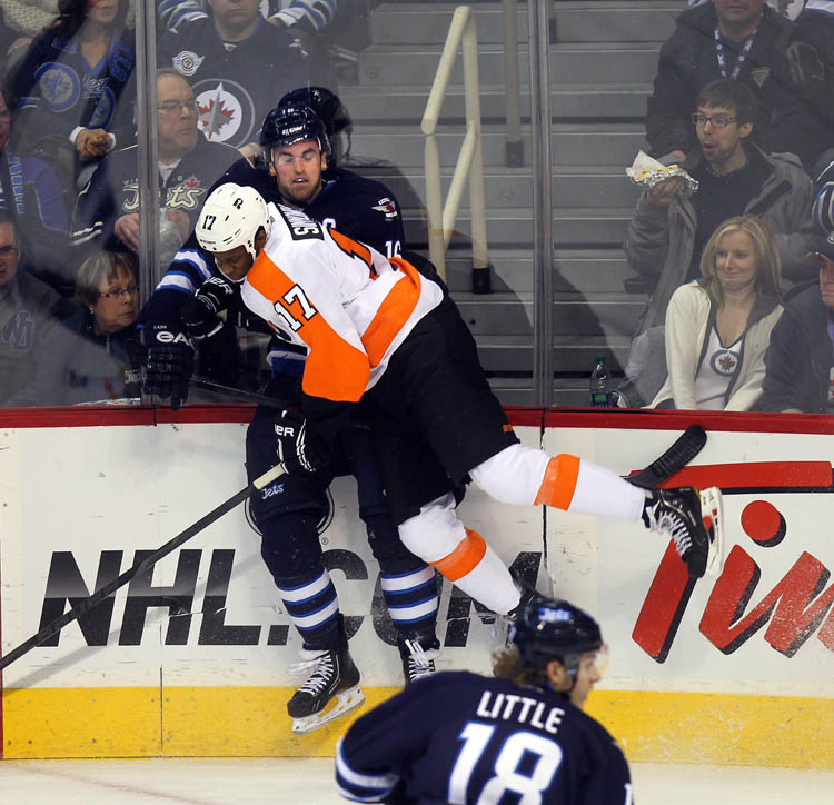Winnipeg Jets' Captain Andrew Ladd takes a hit from Philadelphia Flyers' Wayne Simmonds Tuesday night at MTS Centre. (Phil Hossack / Winnipeg Free Press)