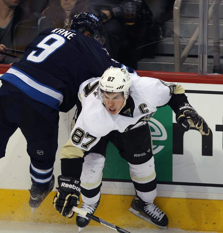 Pittsburgh Penguins captain Sidney Crosby is tied up by Winnipeg Jets Evander Kane during third period NHL action in Winnipeg. The Jets lost the game 3-1. (JOE BRYKSA / WINNIPEG FREE PRESS)