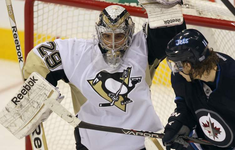 Pittsburgh Penguins goaltender Marc-Andre Fleury holds the net as Winnipeg Jets  Bryan Little moves in during third period NHL action in Winnipeg. The Jets lost the game 3-1. (JOE BRYKSA / WINNIPEG FREE PRESS)