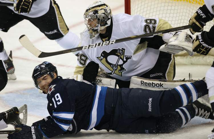 Winnipeg Jets Jim Slater gets sent to the ice by a cross check in front of Pittsburgh Penguins goaltender Marc-Andre Fleury during first period NHL action Friday night in Winnipeg.    (JOE BRYKSA / WINNIPEG FREE PRESS)