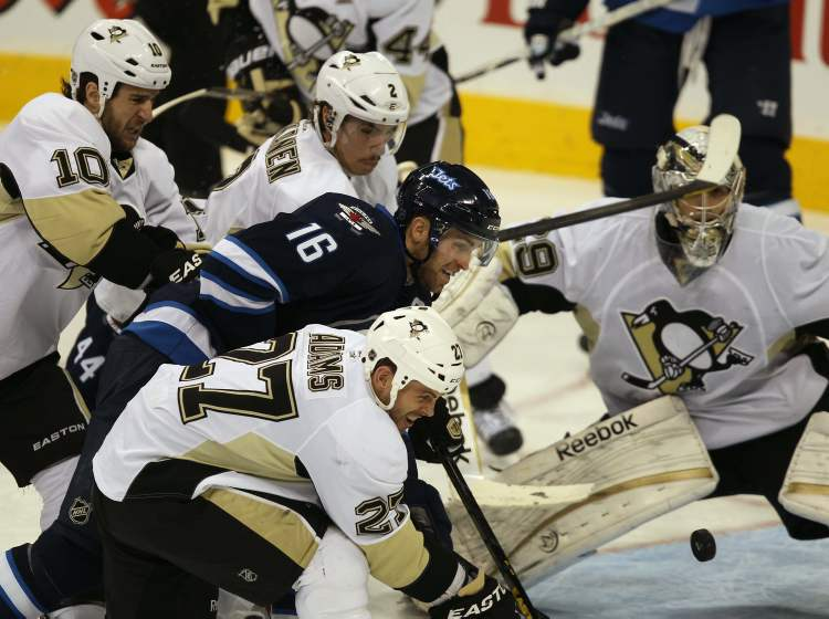 Pittsburgh Penguins Chris Kunitz, left, Matt Niskanen, centre-rear, and Craig Adams tie up Winnipeg Jets captain Andrew Ladd in front of Pens goaltender Marc-Andre Fleury during third period NHL action in Winnipeg. The Jets lost the game 3-1.