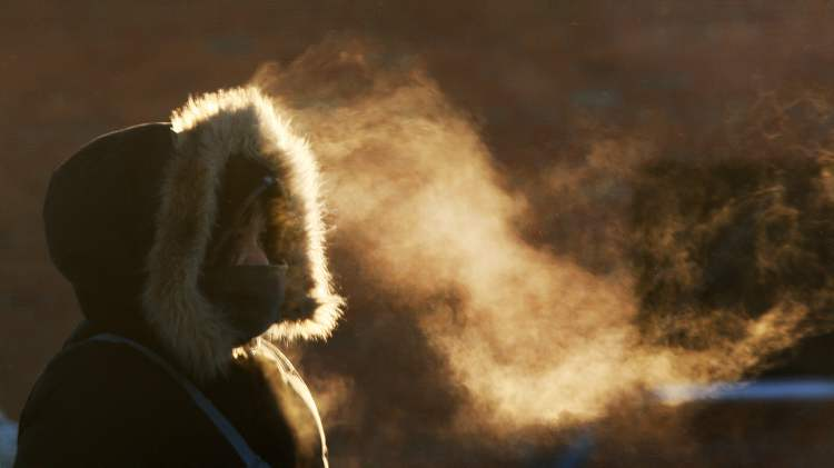 A woman emits frosty breath from her parka this morning while waiting for a bus on Isabel Street.