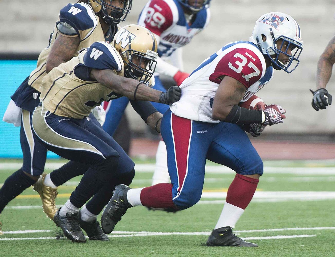 Winnipeg Blue Bombers' Demond Washington, left, grabs Montreal Alouettes' Tyrell Sutton during second half CFL football action in Montreal Monday. (Graham Hughes / The Canadian Press)