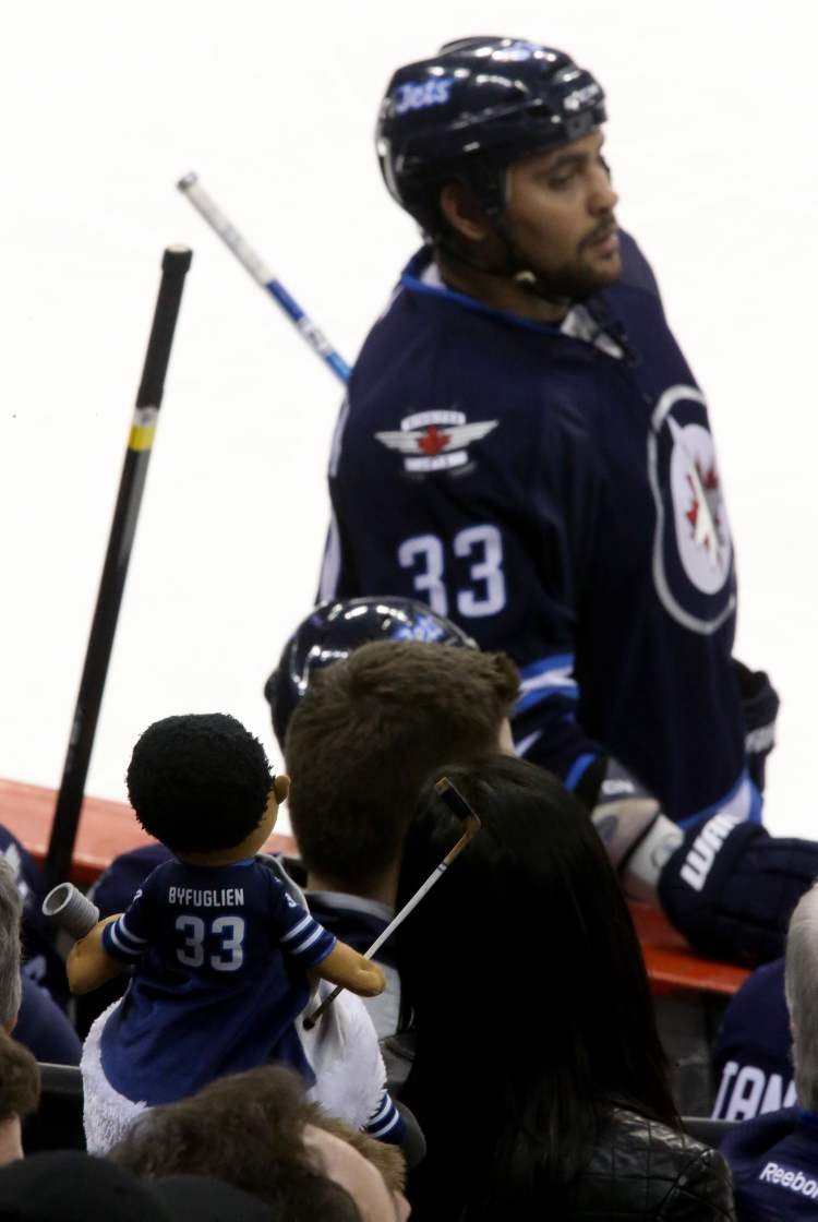 A fan wearing a Dustin Byfuglien hgat watches as the Jets' defenseman skates by during Saturday's game.