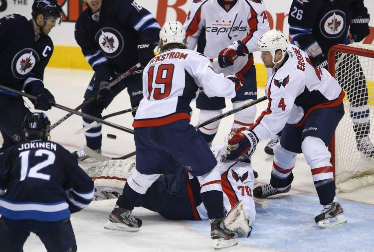 Winnipeg Jets and Washington Capitals skaters scramble for the puck around Washington Capitals goaltender Braden Holtby late in Saturday afternoon's game. (TREVOR HAGAN / WINNIPEG FREE PRESS)