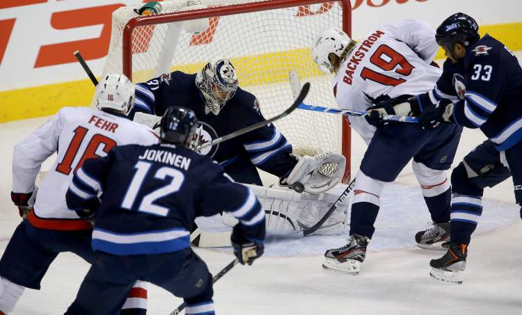 Winnipeg Jets' goaltender Ondrej Pavelec stops Washington Capitals' Nicklas Backstrom in front of the net as he battles with Dustin Byfuglien (33) in the first period of Saturday's game. Washington Capitals' Eric Fehr and Winnipeg Jets' Olli Jokinen look on.