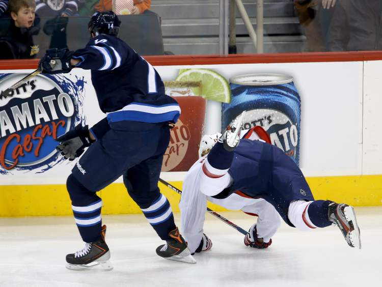 Winnipeg Jets forward Anthony Peluso dumps Washington Capitals forward Nicklas Backstrom early in the first period of Saturday's game at the MTS Centre. (TREVOR HAGAN / WINNIPEG FREE PRESS)