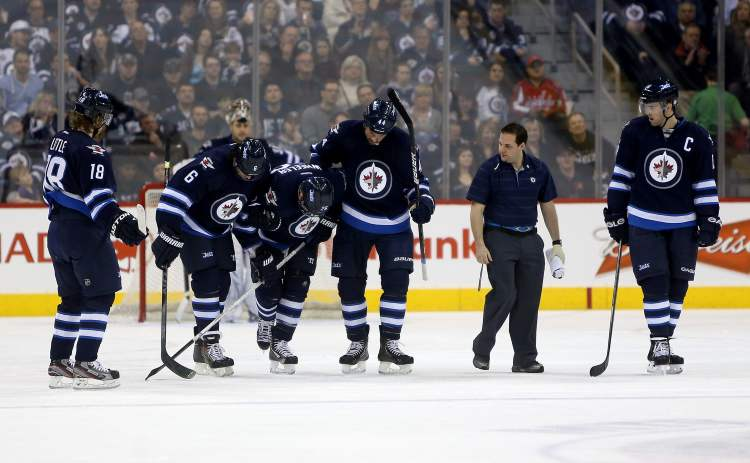 Winnipeg Jets' Ron Hainsey (6) and Zach Bogosian (44) assist Blake Wheeler off the ice in the second period of Saturday's game against the Washington Capitals, as Bryan Little (18), a trainer and Andrew Ladd (16) look on.