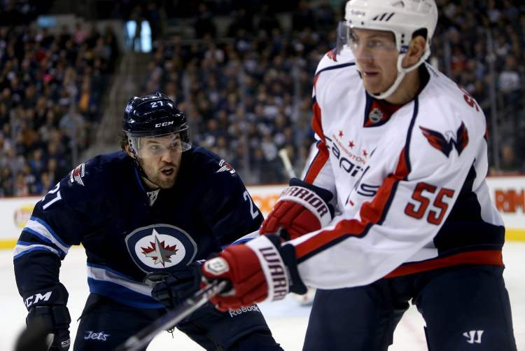 Winnipeg Jets forward Eric Tangradi lines up Washington Capitals' Jeff Schultz for a big hit during the second period Saturday's game. (TREVOR HAGAN / WINNIPEG FREE PRESS)