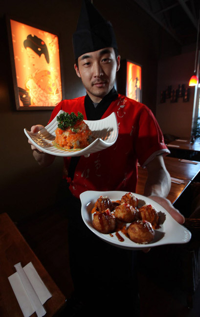 Chef Woo Can (right) serves Volcano Roll (top) and takoyaki at Sushi Ai.