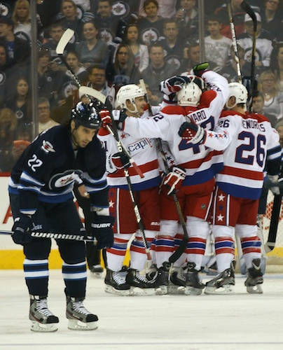 Winnipeg Jets forward Chris Thorburn skates by as a group of Washington Capitals celebrate a goal in the second period. (JOE BRYKSA / WINNIPEG FREE PRESS)