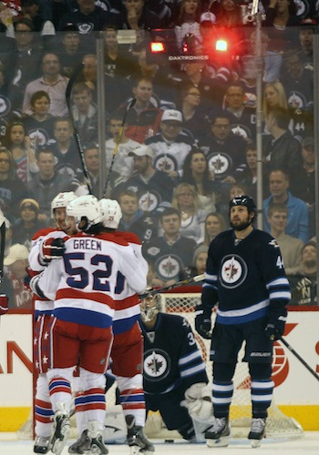 Winnipeg Jets defenceman Zach Bogosian and goaltender Ondrej Pavelec watch as Jay Beagle of the Washington Capitals is mobbed by teammates after scoring during the second period Friday night.