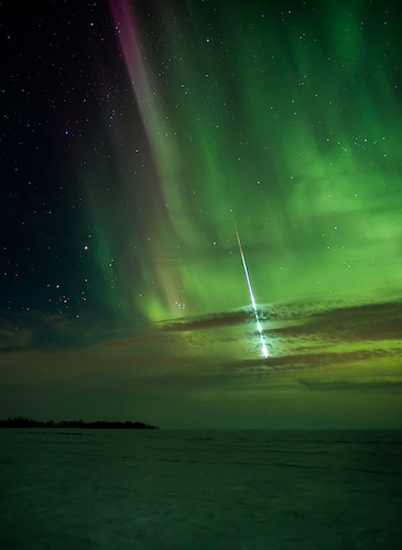 A meteor is captured streaking through the sky and the shimmering northern lights.