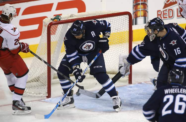 Carolina Hurricanes' Alexander Semin (28) puts the puck past Winnipeg Jets' Dustin Byfuglien (33) and goaltender Ondrej Pavelec (31) early in the first period of NHL action at the MTS Centre in Winnipeg, Saturday.