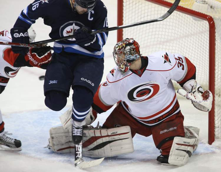 Carolina Hurricanes' Brett Bellemore (73) tries to clear Winnipeg Jets' Andrew Ladd (16) as he tries to screen a shot on Hurricanes goaltender Justin Peters (35) during the first period at the MTS Centre in Winnipeg, Saturday. (TREVOR HAGAN / WINNIPEG FREE PRESS)