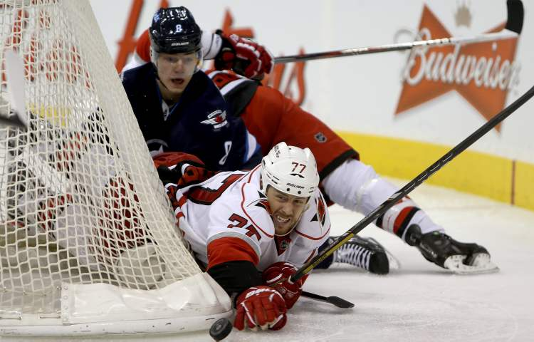 Winnipeg Jets' Alexander Burmistrov looks on as Carolina Hurricanes' Joe Corvo hits the puck with his hand behind the Carolina net during the second period.