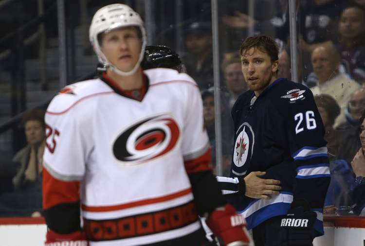 Winnipeg Jets' Blake Wheeler (26) stares at Carolina Hurricanes' Joni Pitkanen after a skirmish in front of the Hurricanes net during the second period.