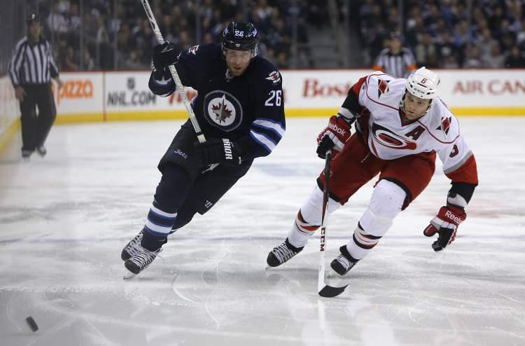 Winnipeg Jets' Blake Wheeler (26) and  Carolina Hurricanes' Tim Gleason (6) race to the puck during second-period action. (TREVOR HAGAN / WINNIPEG FREE PRESS)